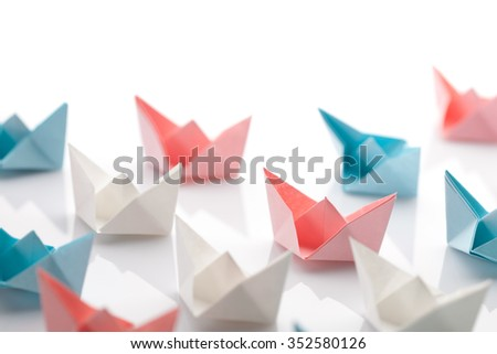 Leadership concept using blue paper ship among white - stock photo