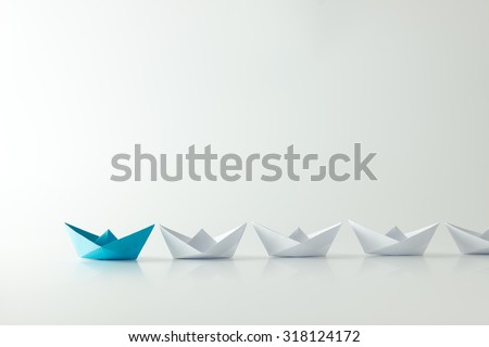 Leadership concept with blue paper ship leading among white - stock photo