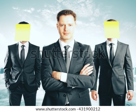 Leadership concept with handsome caucasian businessman in front of businesspeople with covered faces on abstract background - stock photo