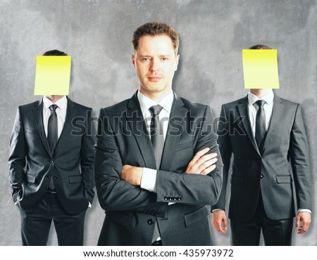 Leadership concept with handsome caucasian businessman in front of businesspeople with covered faces on concrete background - stock photo