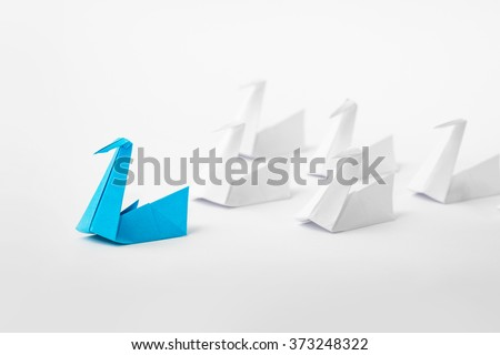 Leadership concept with origami paper bird leading among white.