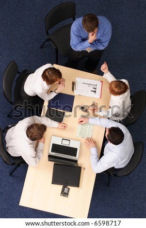 leadership - five business people meeting - Businesspeople gathered around a table for a meeting, brainstorming. Aerial shot taken from directly above the table. - stock photo