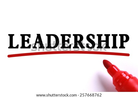 Leadership text is on white paper with red underline which is written by the red marker. - stock photo