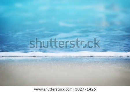 Leading edge of a gentle summer resort beach wave. Shallow depth of field.  - stock photo