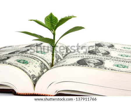 Leaf bud growing out of a book covered with dollars - symbol of education costs and benefit (focus on the portrait in foreground) - stock photo