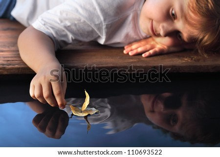 leaf ship in children hand, focus on hand - stock photo