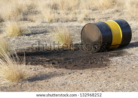 Leaking oil barrel wasting nature - stock photo