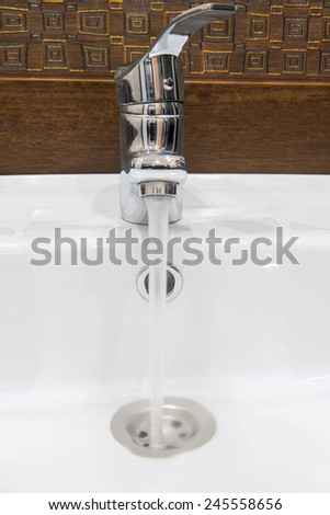leaks water from the tap into the sewer - stock photo