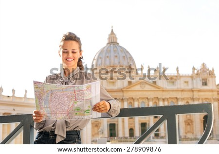 Leaning against a balustrade, a smiling woman tourist is holding and reading a map of Vatican City. In the background is St. Peter's Basilica. - stock photo