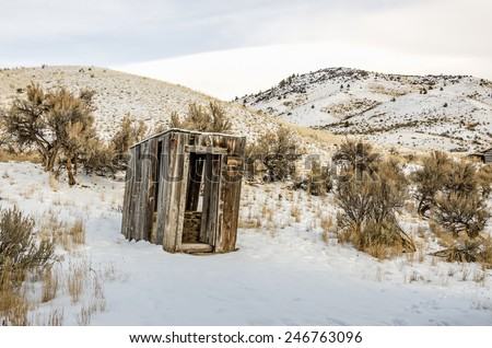 Leaning outhouse with a rusty horseshoe hanging on the corner on a winter day - stock photo
