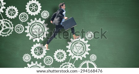 Leaping businessman against green chalkboard