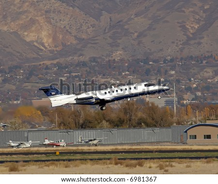 Learjet taking off from small runway gear down - stock photo