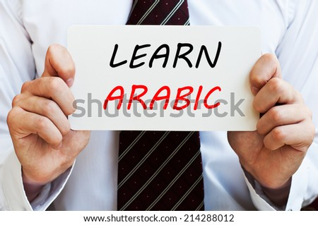 Learn Arabic - man wearing a shirt and a tie holding a signboard with a text on it. Education concept. - stock photo