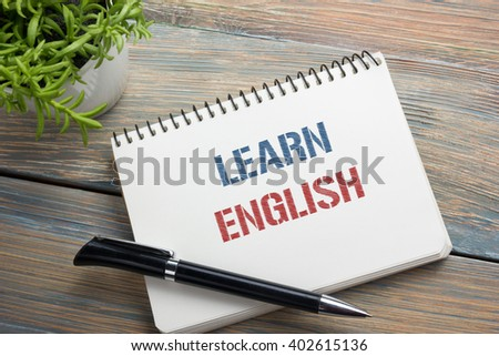 Learn English Text written on notebook page, red pencil and coffee cup. Office desk table top view - stock photo