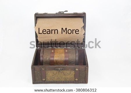 learn more is written on the brown torn paper in the treasure box. isolated on white background