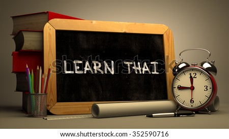 Learn Thai - Inspirational Quote on a Chalkboard. Composition with Chalkboard and Stack of Books, Alarm Clock and Rolls of Paper on Blurred Background. Toned Image. - stock photo
