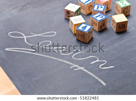 Learn Written Out on a Chalk Board with Blocks - stock photo