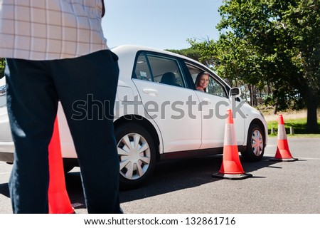 Learner driver girl with instructor taking lessons - stock photo