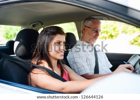 Learner driver student driving car with instructor. happy and confident smiling girl - stock photo
