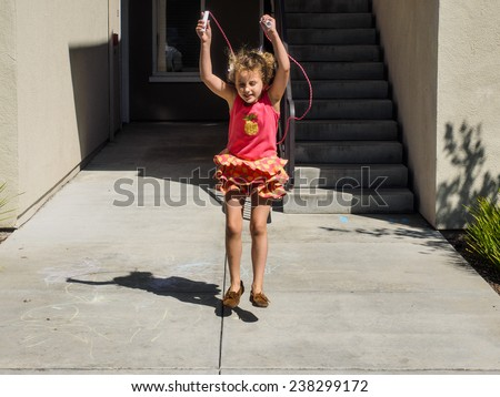 Learning how to jump rope on sunny summer day. - stock photo