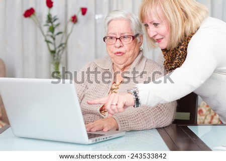 Learning Internet. Daughter teaches her elderly mother using a computer - stock photo