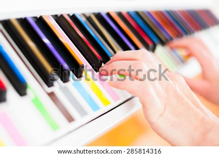 Learning to Play white piano with multy colour keys - stock photo
