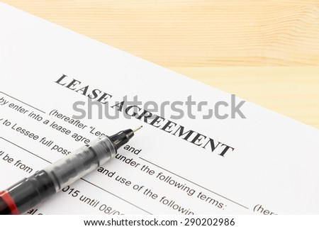 Lease agreement contract sheet and brown pen at bottom left corner on wood table background - stock photo