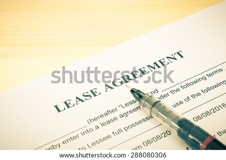 Lease agreement contract sheet and brown pen at bottom right corner on wood table background in vintage style - stock photo