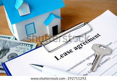 Lease agreement document with dollars and home model. - stock photo