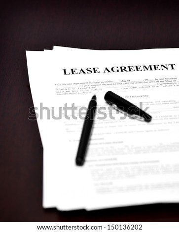 Lease Agreement on desk with black pen waiting to be signed - stock photo
