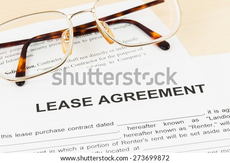 Lease agreement with glasses; document and information are mock-up - stock photo
