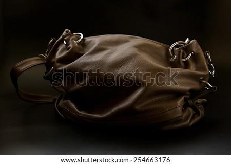 Leather bag on black background. - stock photo