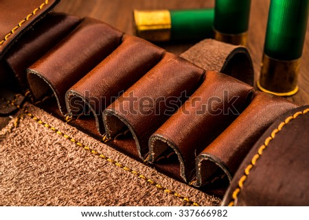 Leather bandolier and hunting cartridges of 12 gauge on the wooden table. Focus on the bandolier - stock photo
