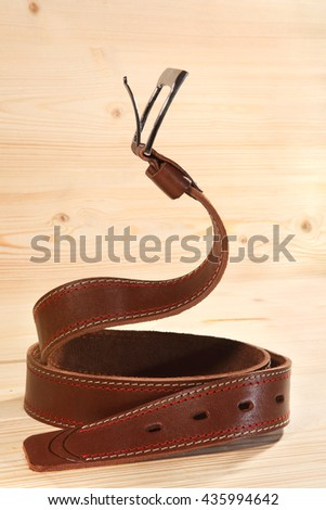 Leather belt for trousers in pose cobra. - stock photo
