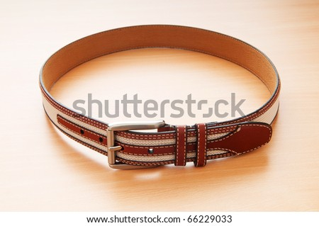 Leather belt on the wooden background - stock photo