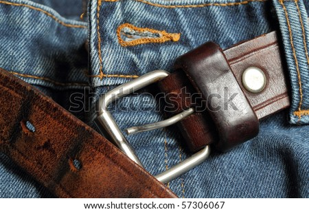 Leather belt unbuckled on a pair of blue jeans - stock photo