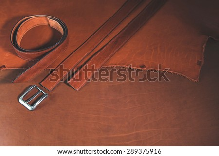 Leather belts with buckle over leather background.