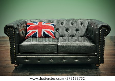 Leather Chesterfield couch with Union jack cushion in empty room with wooden floor and trendy green background - stock photo
