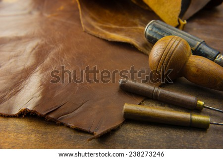 Leather craft. Leather and leather crafting tools on a work table.  - stock photo