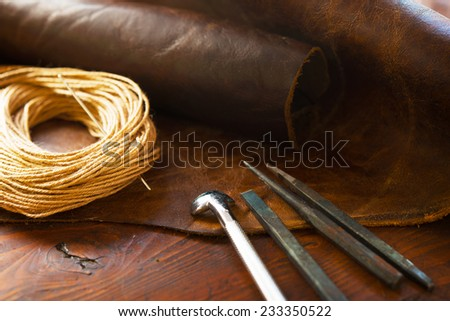 Leather craft. Leather and leather threading or sewing tools on a work table.  - stock photo