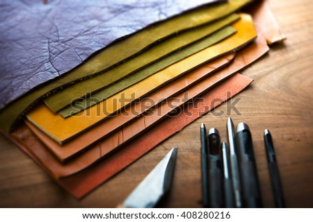 Leather craft or leather working. Selected pieces of beautifully colored or tanned leather on leather craftman's work desk . Piece of hide and working tools on a work table. - stock photo
