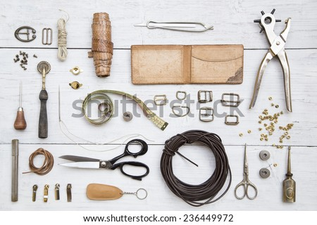 Leather craft tools and utensils on a white wooden background - stock photo
