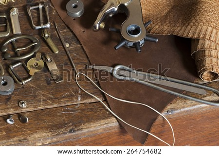 Leather craft tools on a grunge wooden table - stock photo