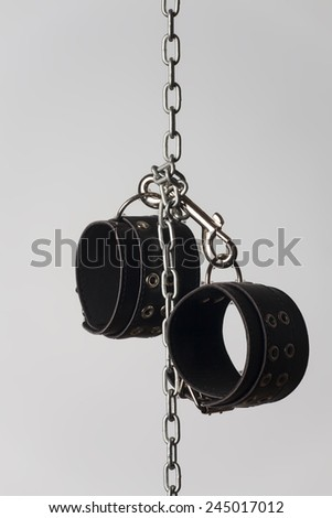 leather cuffs on a chain  - stock photo