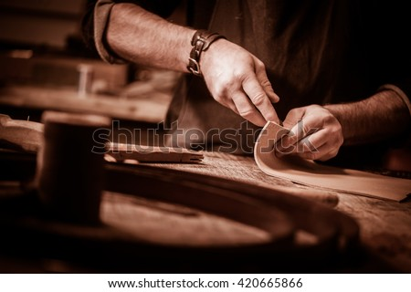 Leather goods craftsman at work in his workshop, France