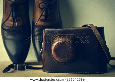 Leather man's shoes and a camera in a leather case