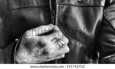 Leather motorcycle jacket with hand using zipper. Motorcycle culture. - stock photo
