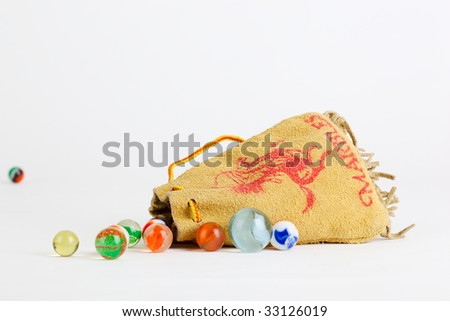 Leather pouch with marbles. - stock photo