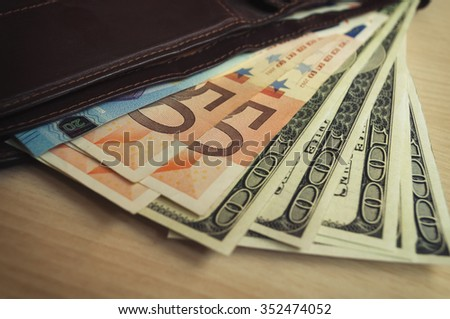 leather purse with banknotes on wooden table