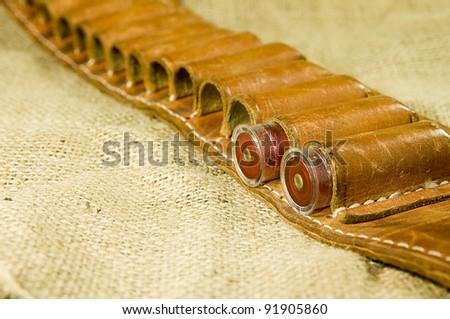 leather shotgun cartridge belt on hessian - stock photo